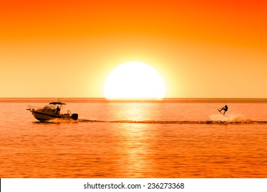 silhouette of motor boat and wakeboarder at sunset performing crazy trick