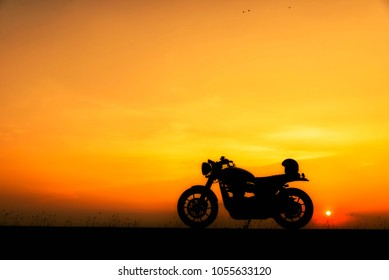 Silhouette of motorbike parking and biker placed helmet on motorcycle with sunset background.Young Traveller man ride motorcycle on highway,Thailand.Trip and lifestyle of motorbike Concept.