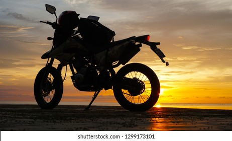Silhouette motorcycle with helmet and bag against sunset background.