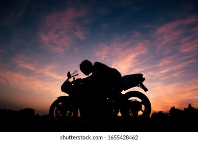 Silhouette of a motorcyclist above his racing motorcycle. Fiery sunset