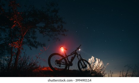 Silhouette of mountain bicycle on a background of the sky.  Bicycle stands on the hill, while cyclist rests. Headlamp and taillight are glowing on the mountain bike.