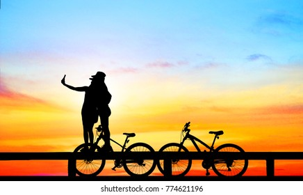 silhouette  Mountain bike and love couple in  the holiday on sunrise time