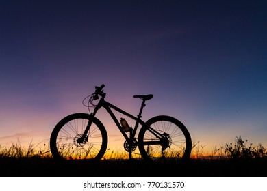 A silhouette of mountain bike at sunset time, along with grass on the ground as a background.