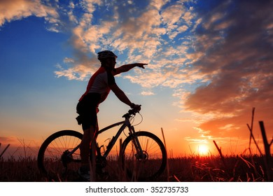 Silhouette of mountain biker against sunrise with clouds