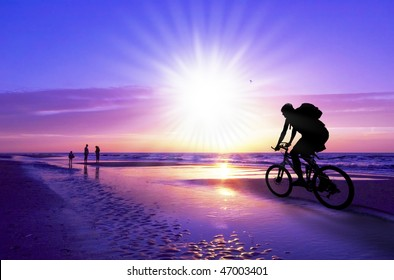 silhouette of a mountain biker on beach and sunset