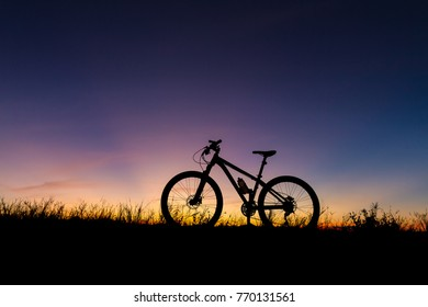 A silhouette of mountain biking at sunset time, along with grass on the ground as a backdrop.