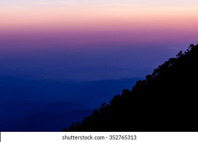 Silhouette of mountain slope Tajamulco with trees in front purple pink blue sunset close to Quetzaltenango in Guatemala