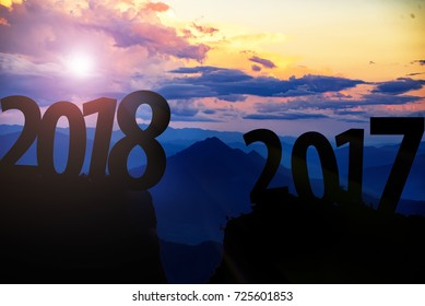 Silhouette of mountain at sunrise between Text 2017 and 2018 years. New year