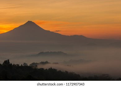 Silhouette of a mountain surrounded by morning mist in Magelang, Indonesia.