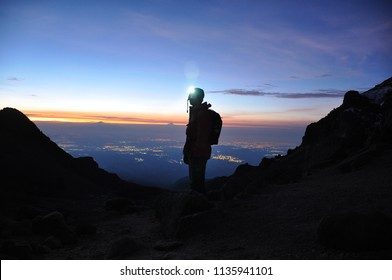 Silhouette of a Mountaineer standing on a Mountain in front of the Horizon with Headtorch on Mount Iztaccihuatl Volcano, Mexico