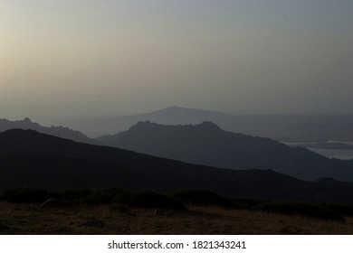 silhouette of the mountains at sunrise with mist.