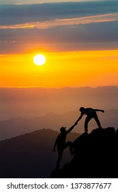 Silhouette in mountains, sunrise. Teamwork of two men hiker helping each other on top of mountain climbing team beautiful sunrise landscape