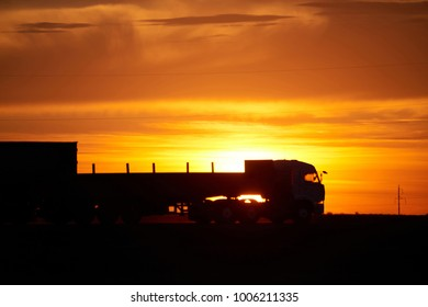 Silhouette of a moving truck at sunset.