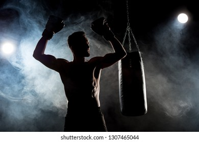 silhouette of muscular athlete in boxing gloves with hands above head on black with smoke