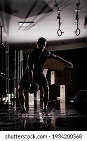 Silhouette of a muscular athlete lifting very heavy weights. Man working out indoors