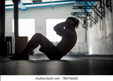 silhouette of Muscular man exercising doing sit up exercise. Athlete with six pack, white male, no shirt