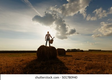 silhouette of musician with guitar at sunset field, music background. It should be on top of the bale or a haystack. Musician happy, free artist, individual freedom
