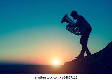 Silhouette of musician playing the tuba on rocky sea coast during amazing sunset. Trumpet.