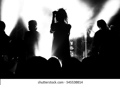 Silhouette of musicians girl with dreadlocks on the stage during a rock concert in front of a crowd of fans. People in the bright light of the lanterns