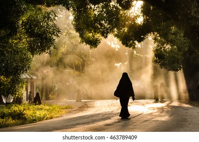 Silhouette of a muslim african woman walking on the road at sunset