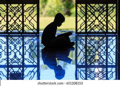 silhouette of a muslim kids reciting Al-quran at mosque.