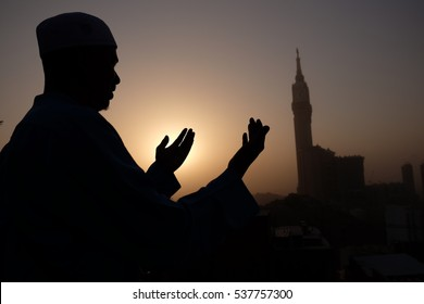Silhouette of muslim man praying (doa) with Makkah Royal Clock Tower in the background.