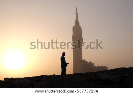 Silhouette of muslim man praying with Makkah Royal Clock Tower in the background.