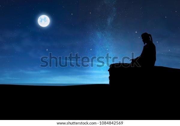 Silhouette of muslim man praying at night