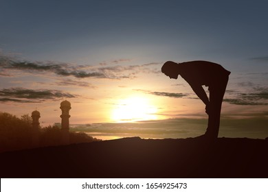 Silhouette of Muslim man in praying position (salat) with a sunset sky background - Shutterstock ID 1654925473
