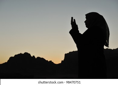 silhouette of a muslim woman praying on the desert