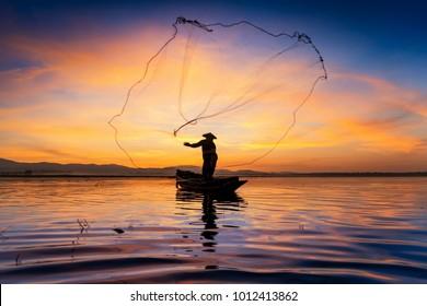 Silhouette of Myanmar fisherman on wooden boat ,Myanmar fisherman in action catching freshwater fish in nature river, Myanmar traditional fishermen at the sunset near Inle lake,Myanmar