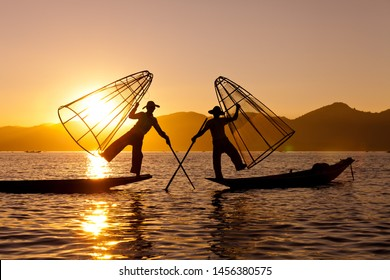 Silhouette of Myanmar fisherman on wooden boat at sunset .Burmese fisherman on bamboo boat catching fish in traditional way with handmade net balancing and paddling with a leg. Inle lake,Myanmar