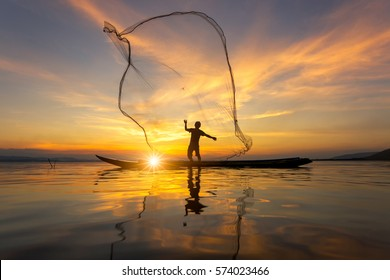 Silhouette of Myanmar fisherman on wooden boat ,Myanmar fisherman in action catching freshwater fish in nature river, Traditional fishermen at the sunset near Inle lake,Myanmar