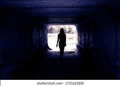 the silhouette of a mysterious woman in the tunnel