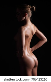 Silhouette of a naked slender young sexy girl on a black background