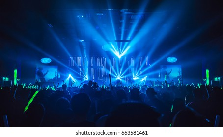 Silhouette in night club under blue rays beam and young people holding light saber enjoying at concert concept.