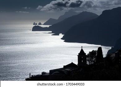 silhouette of Nocelle village (Positano) and Capri island in background seen from the Path of the Gods (Sentiero degli Dei) . Amalfi coast, Positano, Campania, Italy