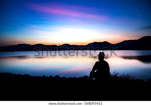 Silhouette of obese men on the lagoon looking at sunrise.