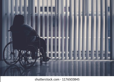 Silhouette of obese woman sitting in the wheelchair by the window. Shot in the hospital