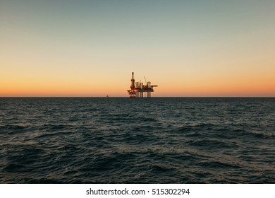Silhouette of Offshore Jack Up Rig in The Middle of The Sea at Sunset Time. For produce oil and gas fuel.
