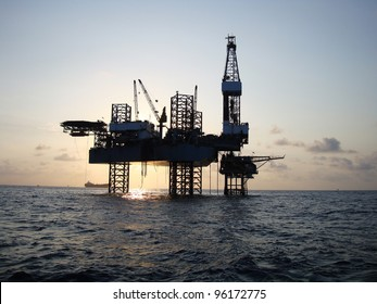 Silhouette of Offshore Jack Up Rig in The Middle of The Sea at Sunset Time