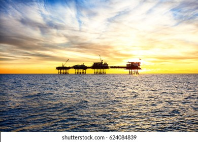 Silhouette of offshore oil platform at sunset