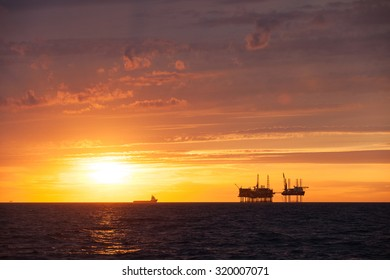 Silhouette of an offshore oil platform and supply vessel at sunset