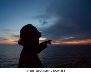 silhouette offshore worker pointing the finger to the sky of sunset background