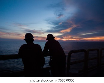 silhouette offshore working crew talking at platform hand rail while looking  the horizon sky at sun set in the evening time