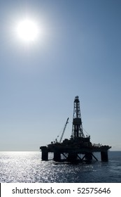 Silhouette of an oil drilling rig in offshore area, during very calm seas and blue sky