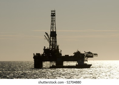 silhouette of an oil drilling rig, in offshore area, with a supply vessel along side and helicopter landed.
