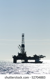 silhouette of an oil drilling rig, in offshore area, with a supply vessel along side and helicopter landed