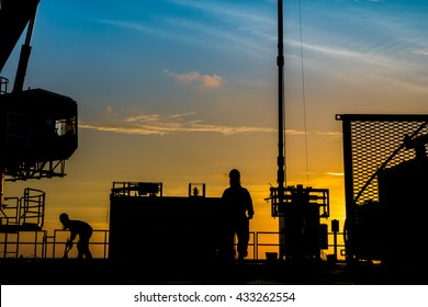Silhouette of oil and gas platform and well service worker while working to perforation production tubing at gas reservoir.