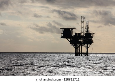 Silhouette of an oil production platform deep in the Gulf of Mexico